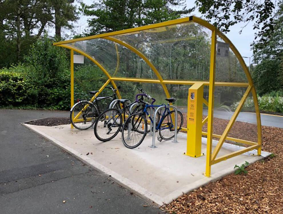 Glass curved bike shelter with electric stations and floor mounts
