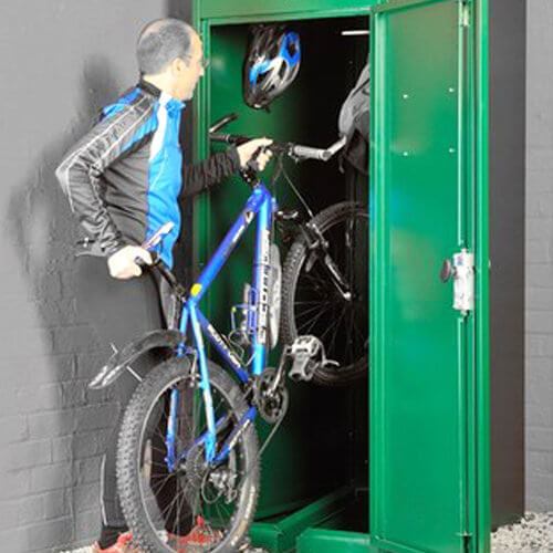 Man putting their bike in a vertical bike locker